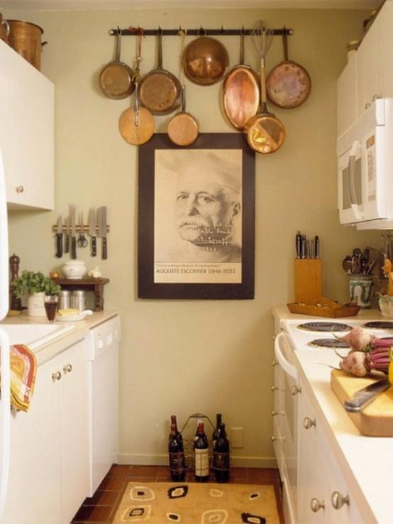 una piccola cucina neutra con armadi cremosi, manopole metalliche, un'opera d'arte e un supporto con pentole vintage