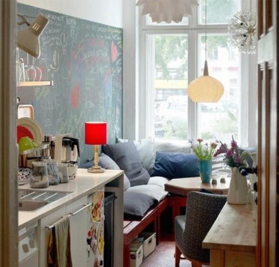 una piccola cucina eclettica con alcuni armadi e un angolo accogliente vicino alla finestra con un tavolo esagonale