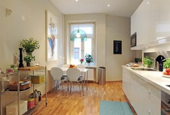 una piccola cucina contemporanea in bianco, con una zona pranzo abbinata e un giro pendente blu puro