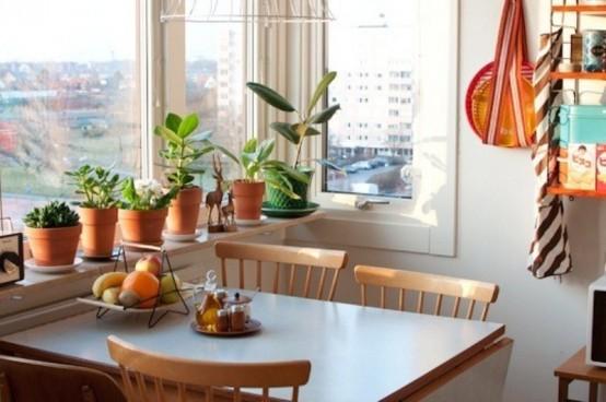 una minuscola sala da pranzo vicino alla finestra con alcune sedie di legno, un tavolo e tanto verde in vasi intorno