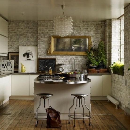 una piccola cucina glam con pareti in mattoni, armadi bianchi e ripiani in metallo, un lampadario in vetro smerigliato