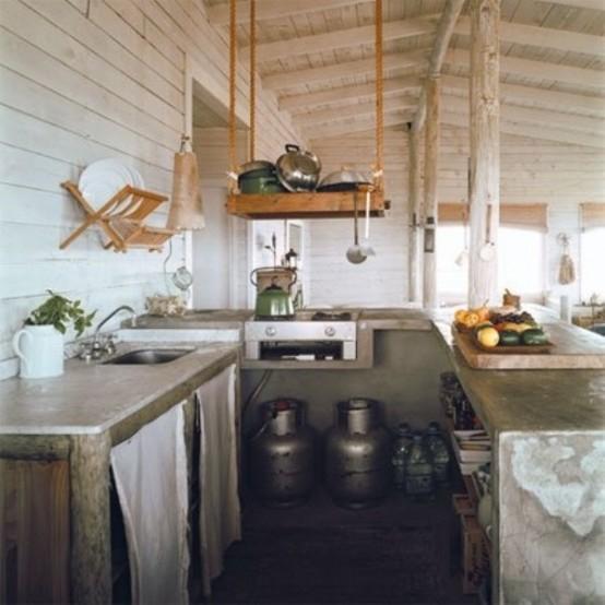 un piccolo rustico incontra la cucina industriale con ripiani in cemento, bidoni in metallo e ripiani in legno sospesi