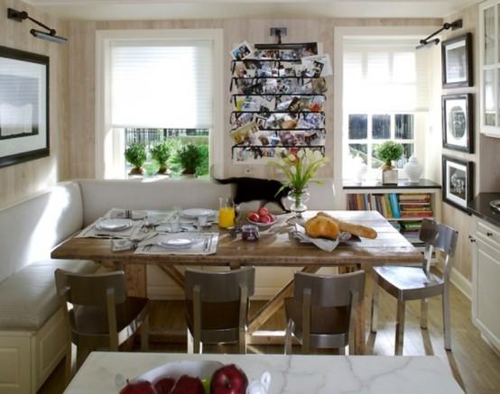 una sala da pranzo con una seduta a forma di L e un tavolo più opere d'arte e un'isola cucina che separa gli spazi