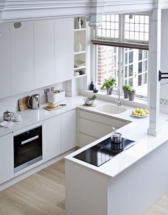 una cucina minimalista bianca con mobili eleganti, senza maniglie, una finestra e semplici elettrodomestici da incasso