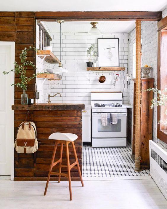 una minuscola cucina in bianco e con superfici in legno ricche di tinte, piante in vaso e un pavimento di piastrelle a mosaico