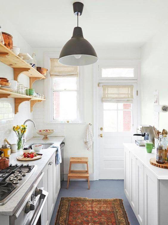 una piccola cucina rustica con mobili bianchi, scaffali aperti, un tappeto stampato, una lampada a sospensione e finestre per la luce naturale