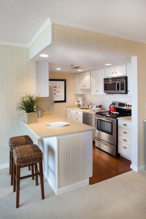 una piccola cucina tradizionale in bianco sporco inserita in un cubo, con un'isola cucina che separa gli spazi