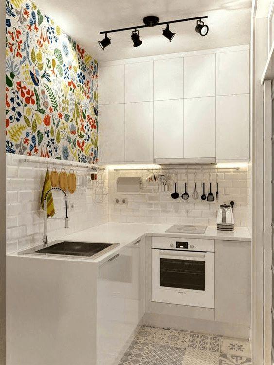 una piccola cucina minimalista con eleganti armadi bianchi, un muro colorato, un backsplash di piastrelle bianche e un pavimento di piastrelle a mosaico