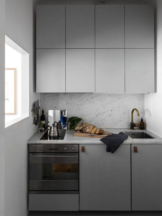 una piccola cucina minimalista con armadi grigio lucido, maniglie in pelle e alzatina in pietra grigia