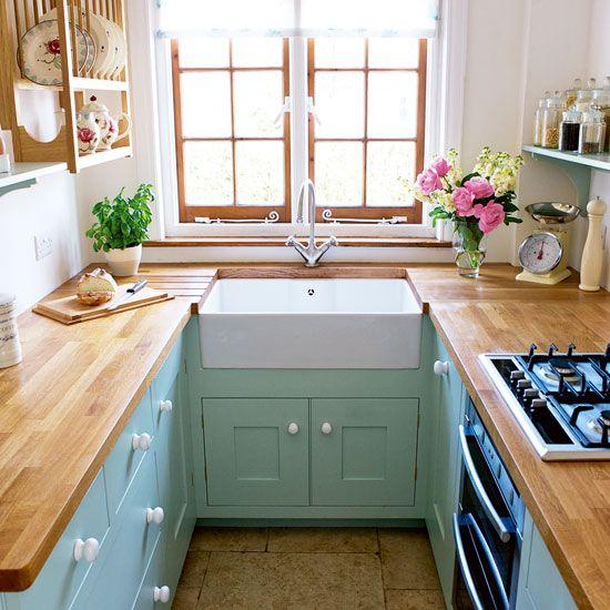 una piccola cucina da fattoria color pastello con mobili alla menta, ripiani da macellaio, scaffali aperti in legno e una finestra con cornice in legno
