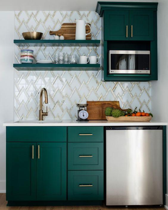 una piccola cucina con armadi color smeraldo, alzatina in mosaico, ferramenta in ottone, scaffali aperti ed elettrodomestici metallici