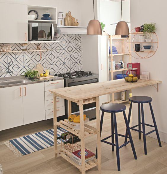 una piccola cucina piena di luce con un backsplash di piastrelle a mosaico, un'isola da cucina con pallet con uno spazio per i pasti, armadi bianchi e tocchi di rame