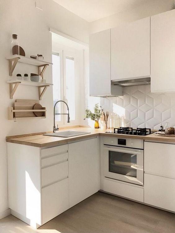 una piccola cucina minimalista con eleganti mobili bianchi, ripiani in legno tinto chiaro, un alzatina in piastrelle bianche, scaffali aperti