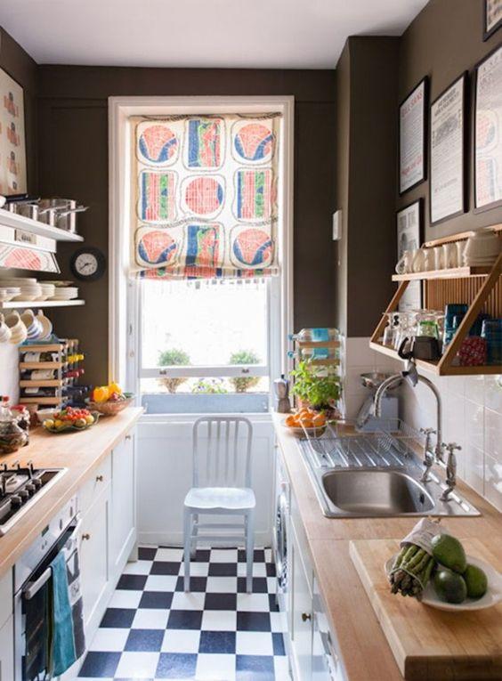 una piccola cucina monocromatica con pareti nere, un backsplash in piastrelle bianche della metropolitana, ripiani in macelleria e una tonalità colorata
