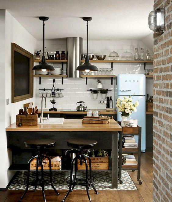 una piccola cucina industriale con armadi neri e un'isola da cucina più ripiani da macellaio, lampade a sospensione nere e un frigorifero blu
