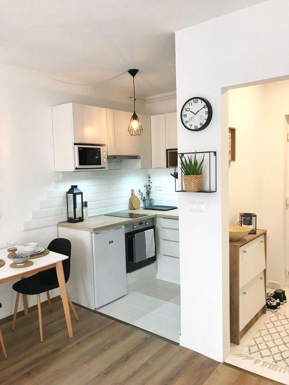 una piccola cucina minimalista con eleganti mobili bianchi, ripiani in legno tinto chiaro, una lampada a sospensione e un pavimento di piastrelle
