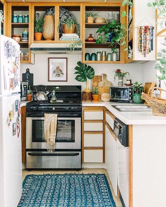 una piccola cucina boho con armadi aperti, lucidi chiusi, un tappeto decorato, molta vegetazione e foglie
