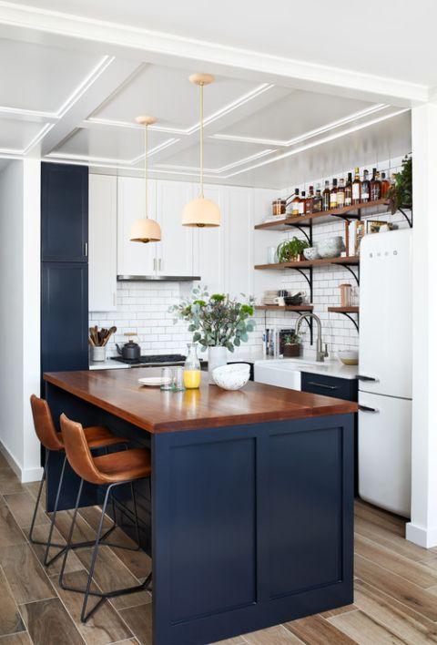 una piccola cucina rustica in bianco e blu scuro, con un'isola cucina con un piano di lavoro colorato, lampade a sospensione e un backsplash in piastrelle della metropolitana