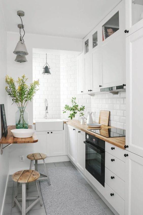 una piccola cucina contemporanea in bianco con pareti fatte con piastrelle, un mini tavolo pieghevole, sgabelli in metallo e legno e lampade a sospensione