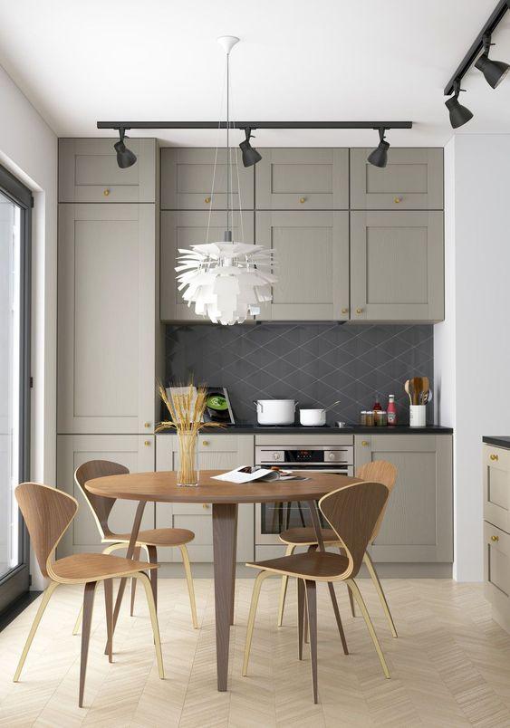 una piccola cucina grigia con un'atmosfera da fattoria, lampade nere, un set da pranzo in compensato per un aspetto laconico e semplice