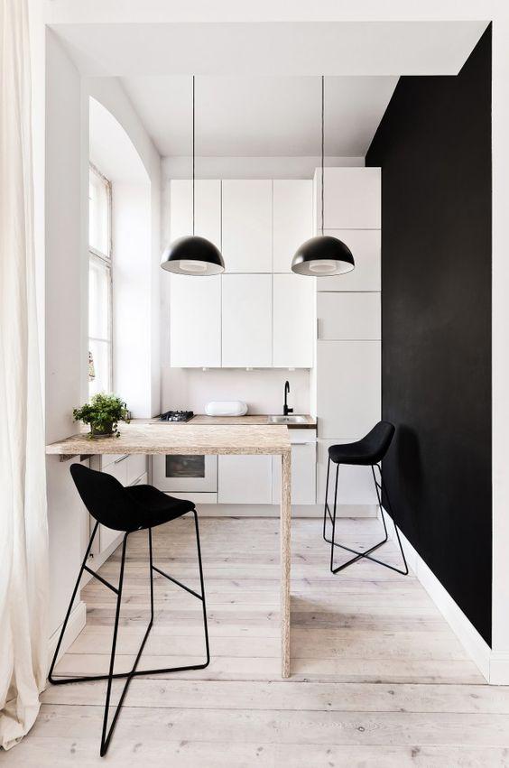 una cucina monocromatica minimalista con eleganti armadi bianchi, lampade a sospensione blakc, un piano di lavoro in compensato, sgabelli neri e un muro nero