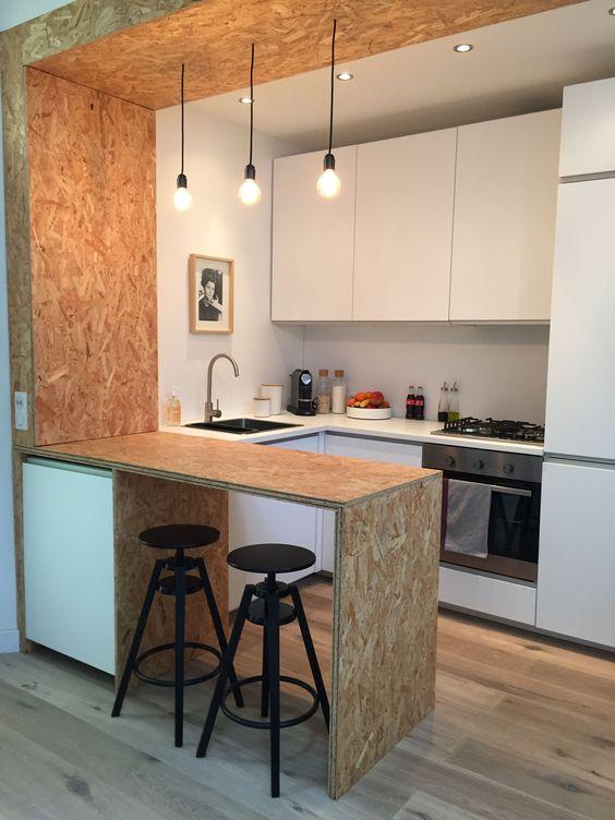 una cucina minimalista con eleganti armadi bianchi, un piano di lavoro in compensato e un pannello sulla parete e sul soffitto, lampadine sospese