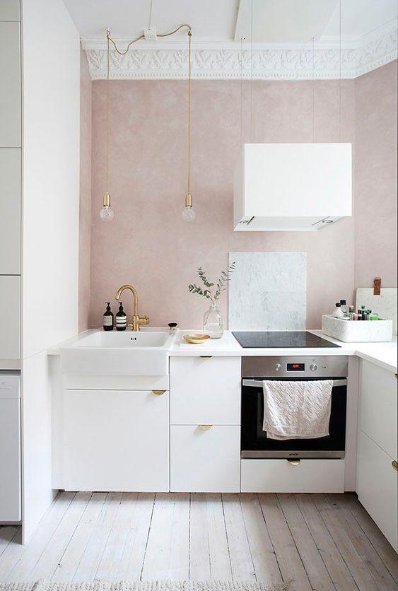 una piccola e serena cucina contemporanea con pareti arrossate, armadi bianchi con maniglie dorate, lampadine a sospensione e un cappuccio bianco