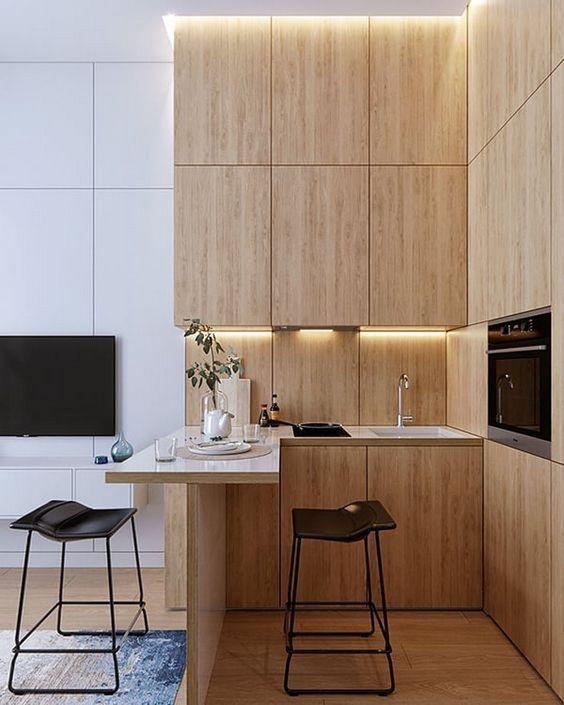 una cucina minimalista con eleganti mobili in compensato, un piano di lavoro per mangiare e cucinare e sgabelli in pelle