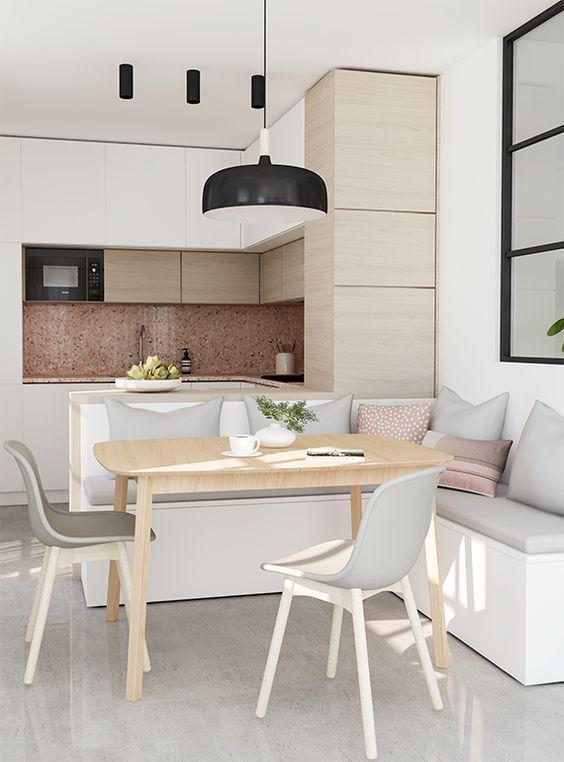 una cucina minimalista con armadi in legno bianco e tinto di luce senza hardware, una lampada a sospensione, un'isola con una panca incorporata