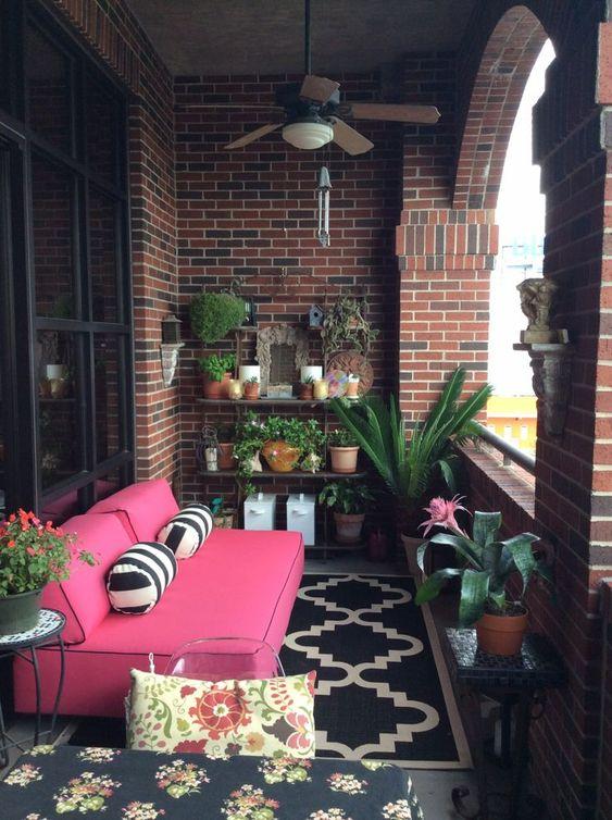 una piccola terrazza luminosa con piante in vaso e fiori, un divano rosa brillante, cuscini e tappeti a motivi geometrici