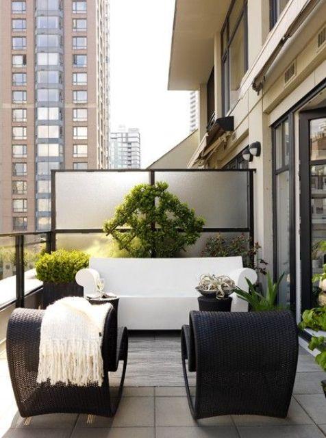 una terrazza monocromatica contemporanea con sedie di vimini nere, un divano bianco, molta vegetazione in vaso