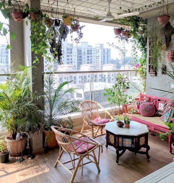 una luminosa terrazza boho con mobili in rattan e tappezzeria colorata, un tavolo in legno intagliato, piante in vaso ovunque
