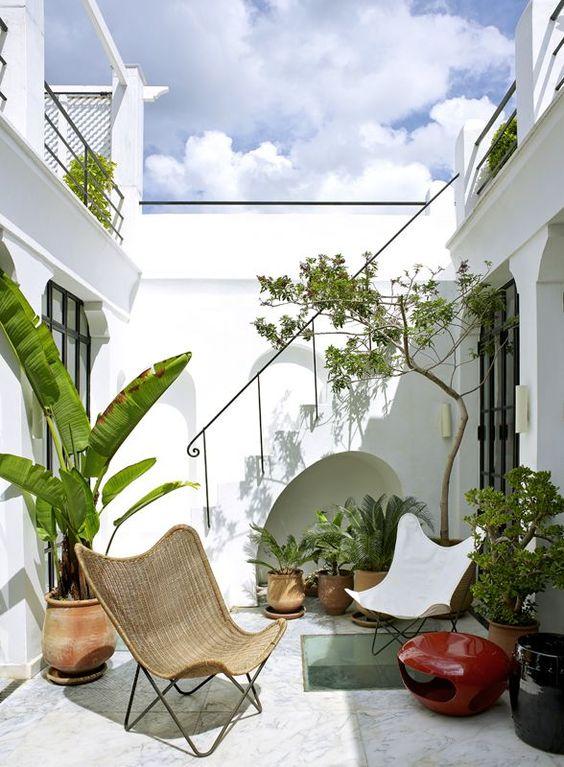una terrazza chic con mobili a farfalla, piante in vaso, un focolare mobile e molta luce naturale