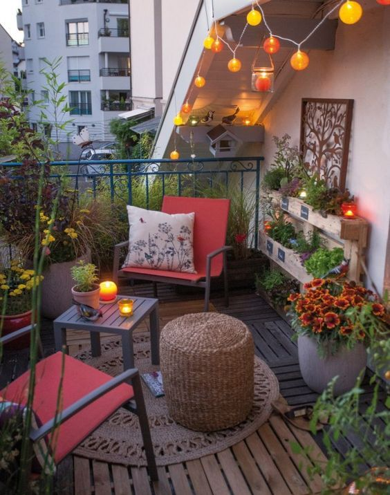 una luminosa terrazza eclettica con un paio di sedie e tavolini, un tappeto, luci e fiori in vaso e vegetazione