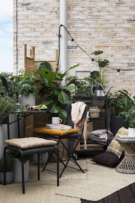 una piccola terrazza boho con mobili in metallo, un tavolo di legno, piante in vaso, luci e uno schermo di legno