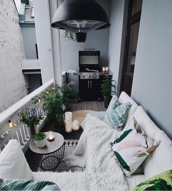 un'accogliente terrazza boho con un divano bianco, cuscini luminosi e una coperta, un tavolino con piante in vaso e fiori più una griglia