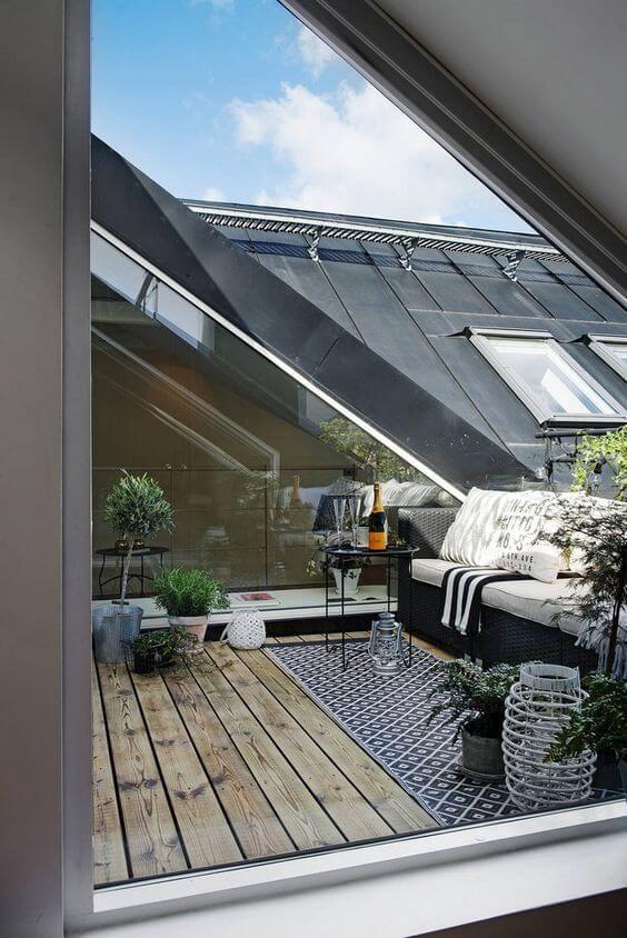 una terrazza scandinava con mobili in vimini scuro, lanterne a candela, piante in vaso, un tavolino da caffè forgiato