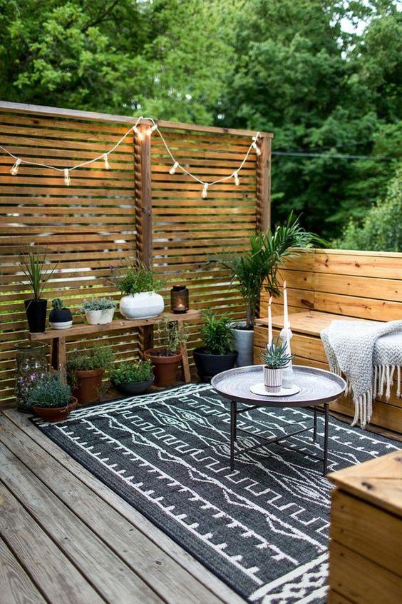 un'accogliente piccola terrazza con mobili in legno, un tavolino da caffè, un tappeto boho, piante in vaso e luci