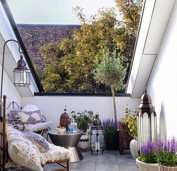 una piccola terrazza boho con varie lanterne a candela, vegetazione in vaso e fiori e sedie forgiate con cuscini boho