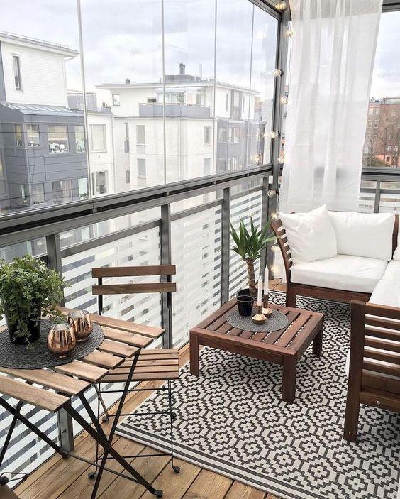 un piccolo balcone contemporaneo con un tappeto geografico, semplici mobili colorati e un po 'di verde