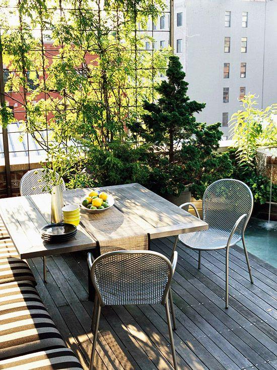 un piccolo e accogliente terrazzo con una panca imbottita, un tavolo in legno, sedie in metallo e un mini giardino in vaso