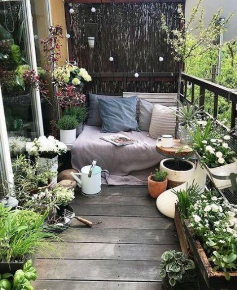 una piccola e fresca terrazza con piante in vaso e fiori, una panchina con coperte e cuscini più un annaffiatoio