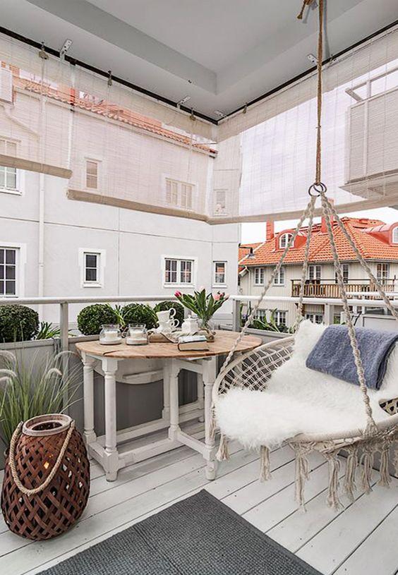 una piccola terrazza boho con una sedia rotonda di vimini con lunghe frange, un tavolo di legno, una lanterna a candela e un tappeto