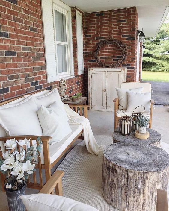 una piccola terrazza della fattoria con mobili imbottiti neutrla, tronchi d'albero come tavolino e piante e fiori in vaso