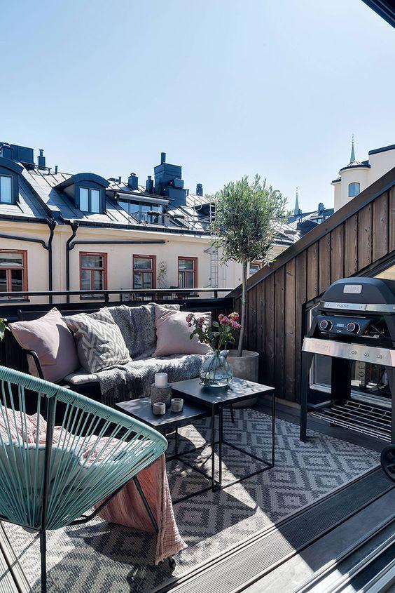 una piccola terrazza contemporanea con tappeti, coperte e cuscini e mobili luminosi e una griglia per gustare cibi freschi alla griglia