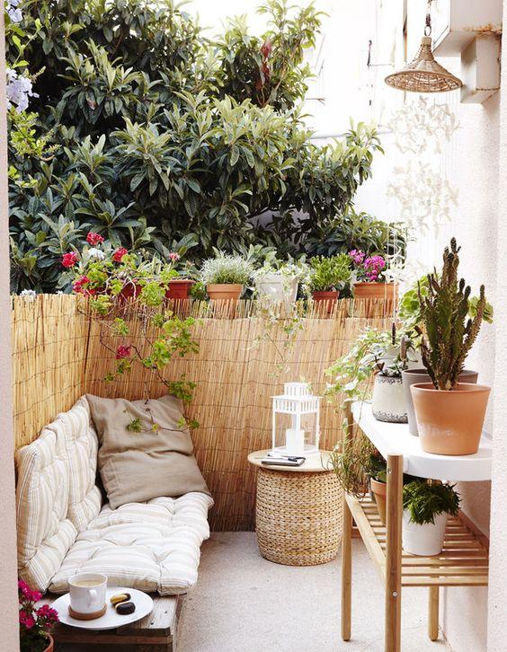 una piccola terrazza boho con una panca imbottita, un pouf in vimini, un grande supporto per piante e molte piante in vaso intorno
