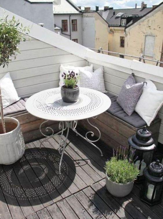 una piccola terrazza scandinava con una panca a forma di L incorporata, un tavolo forgiato, vegetazione in vaso e fiori più lanterne a candela