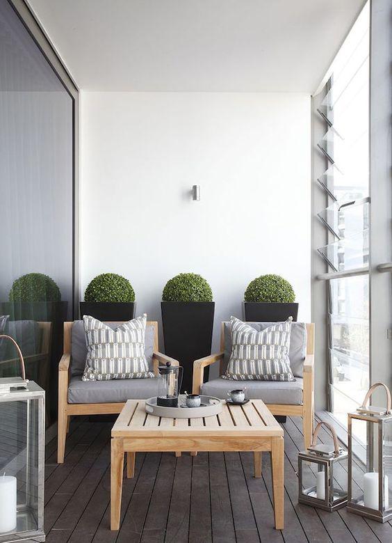 una piccola terrazza contemporanea con semplici mobili in legno, grandi lanterne a candela e bosso in vaso