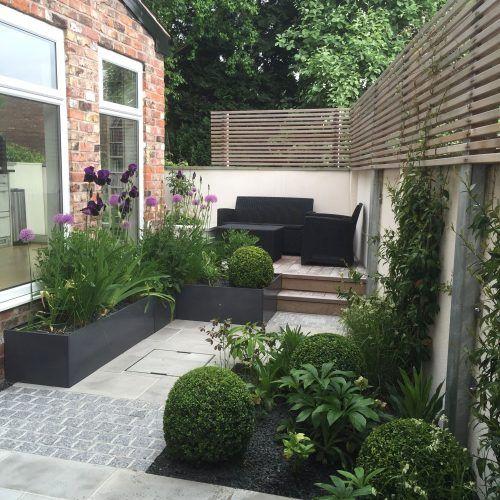 una piccola terrazza contemporanea con mobili scuri, vegetazione in vaso e fiori e schermi in legno per la privacy