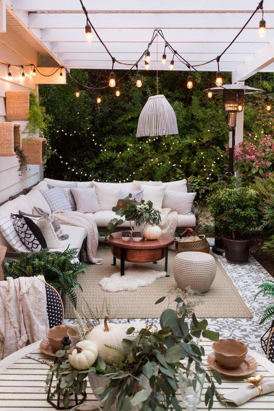 un terrazzino con divano a L, luci e lanterne, una sedia, un tavolino in rame e alcuni pouf